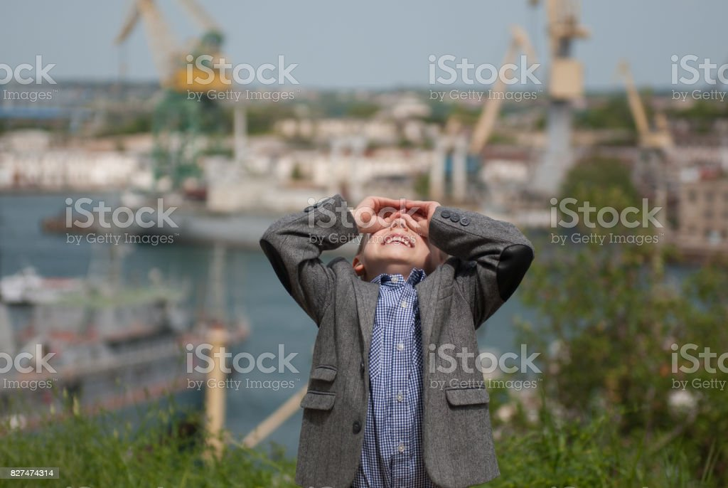 Smiling small kid looking up holding hands in the form of binoculars stock photo