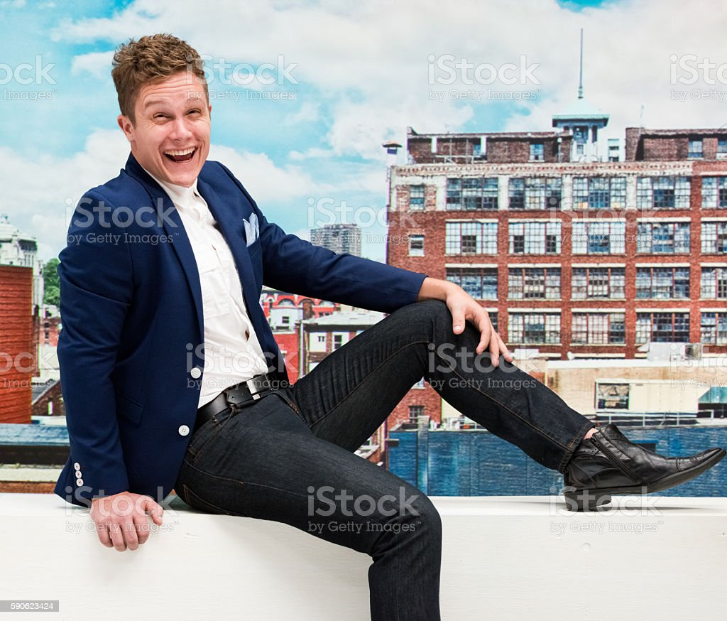 Smiling smart casual man sitting outdoors stock photo