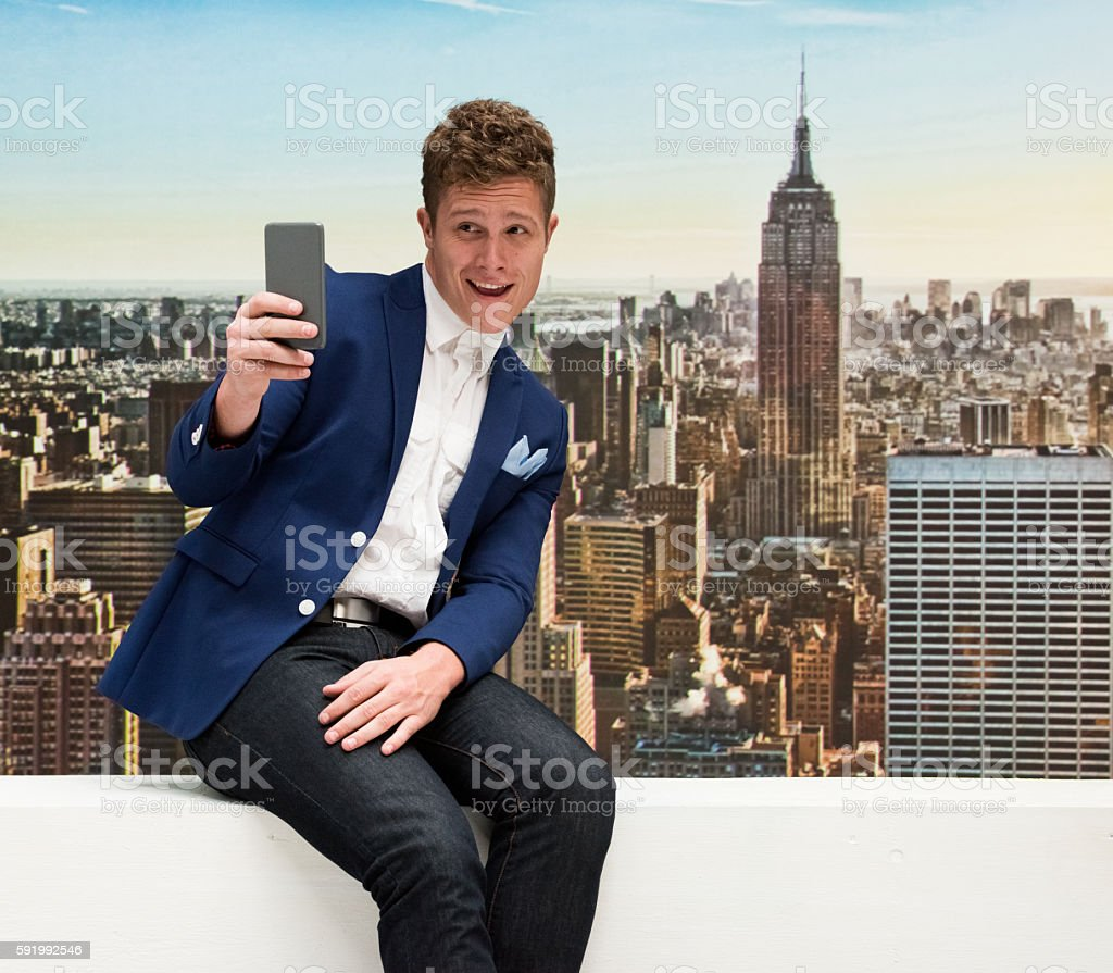 Smiling smart casual man taking a selfie outdoors stock photo