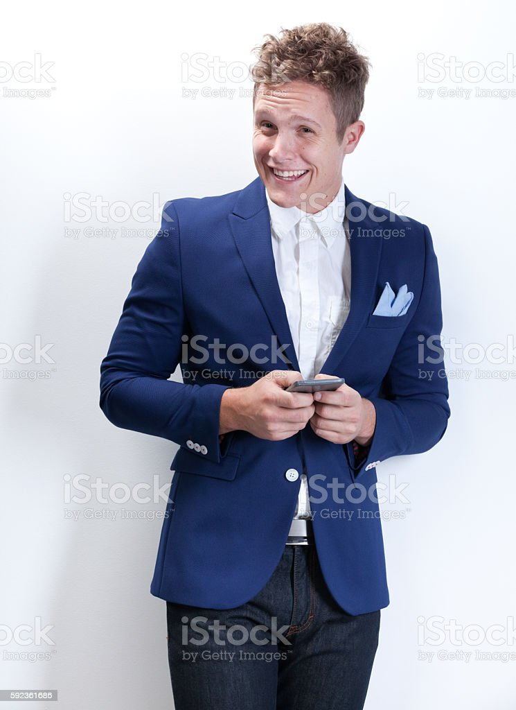 Smiling smart casual man using phone stock photo