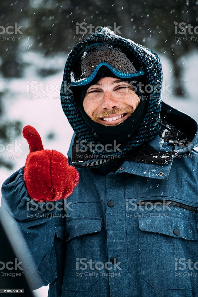 Smiling snowboarder posing stock photo