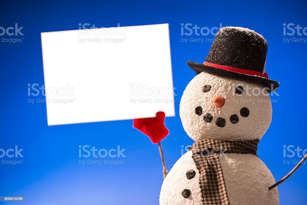 Smiling Snowman wearing Top hat holding blank white sign stock photo