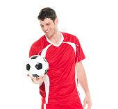 Smiling soccer player holding ball