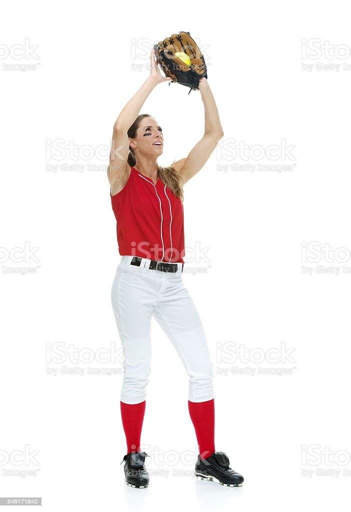 Smiling softball player catching ball stock photo