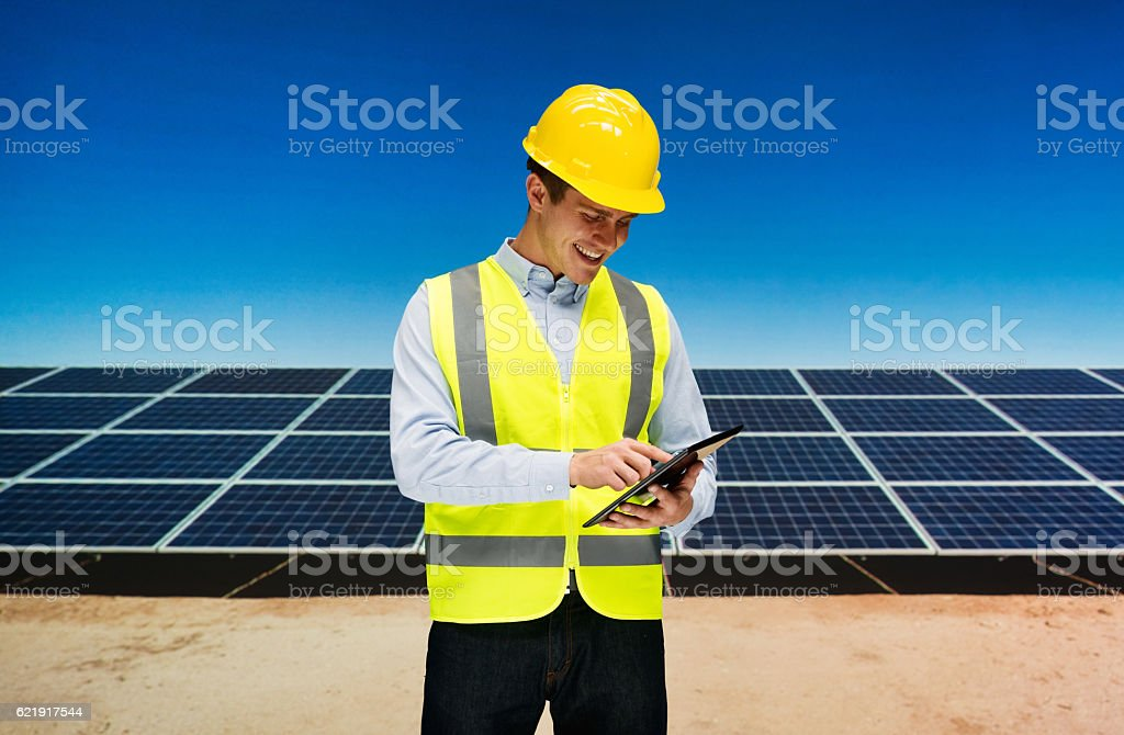 Smiling solar manager using tablet outdoors stock photo