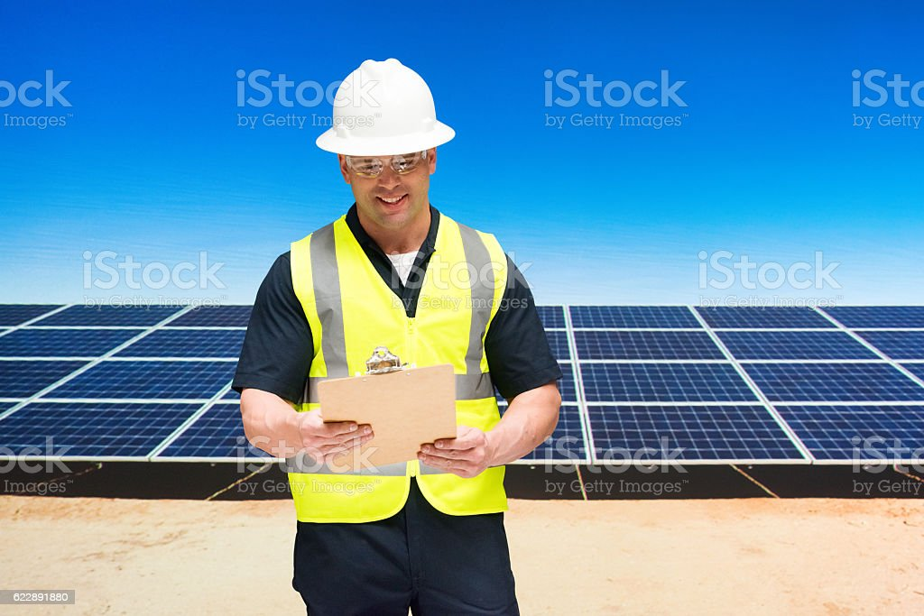 Smiling solar manager working with clipboard stock photo