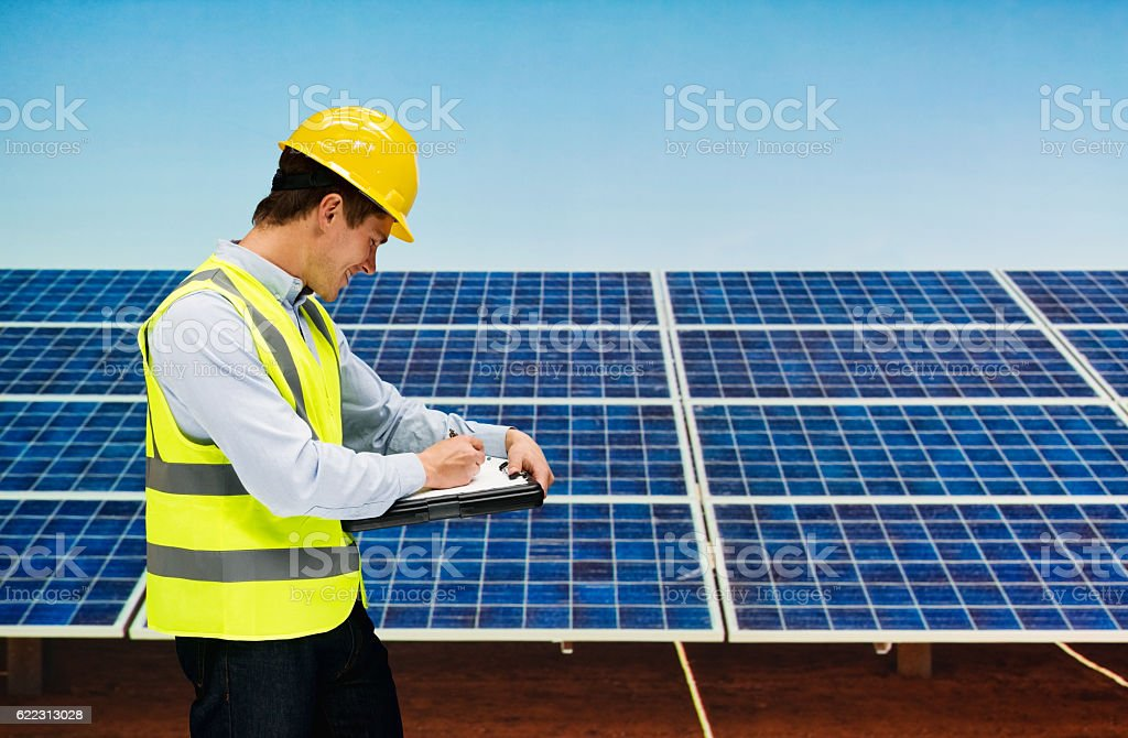 Smiling solar manager writing on clipboard stock photo