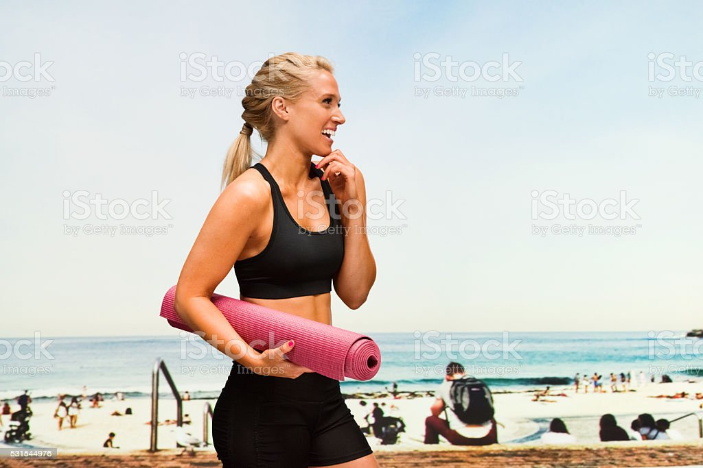 Smiling sports female walking at the beach stock photo