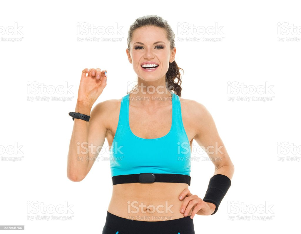 Smiling sports woman holding medicine pill stock photo