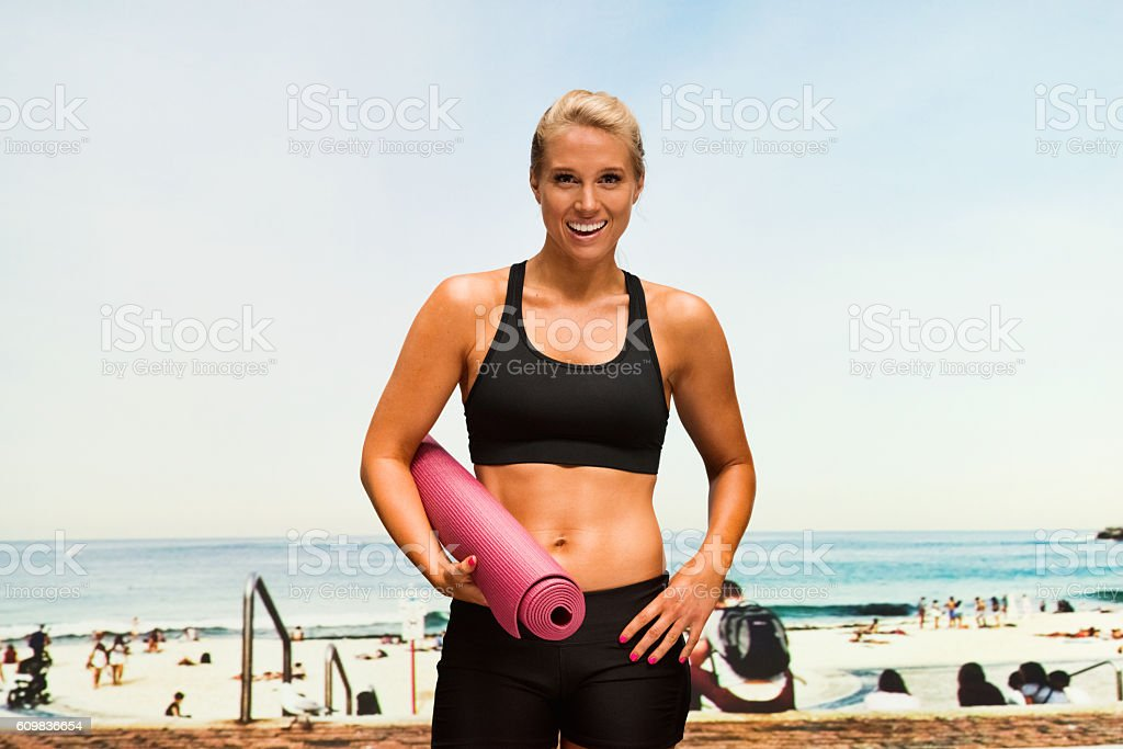 Smiling sports woman standing at the beach stock photo