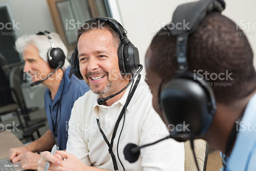 Smiling sportscasters discussing game in the media box stock photo