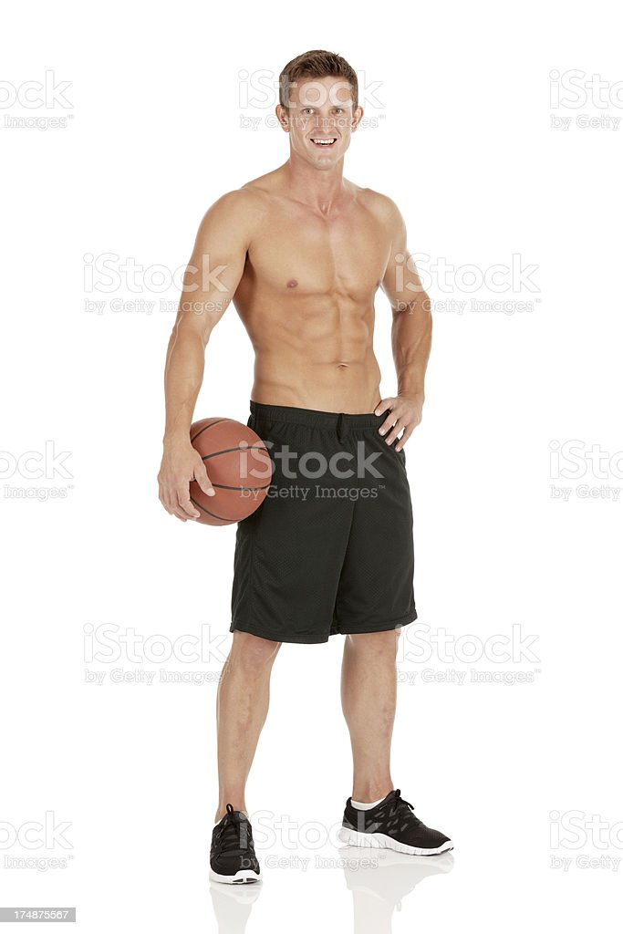 Smiling sportsman holding a basketball royalty-free stock photo