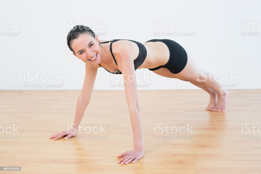 Smiling sporty woman doing push ups in fitness studio stock photo