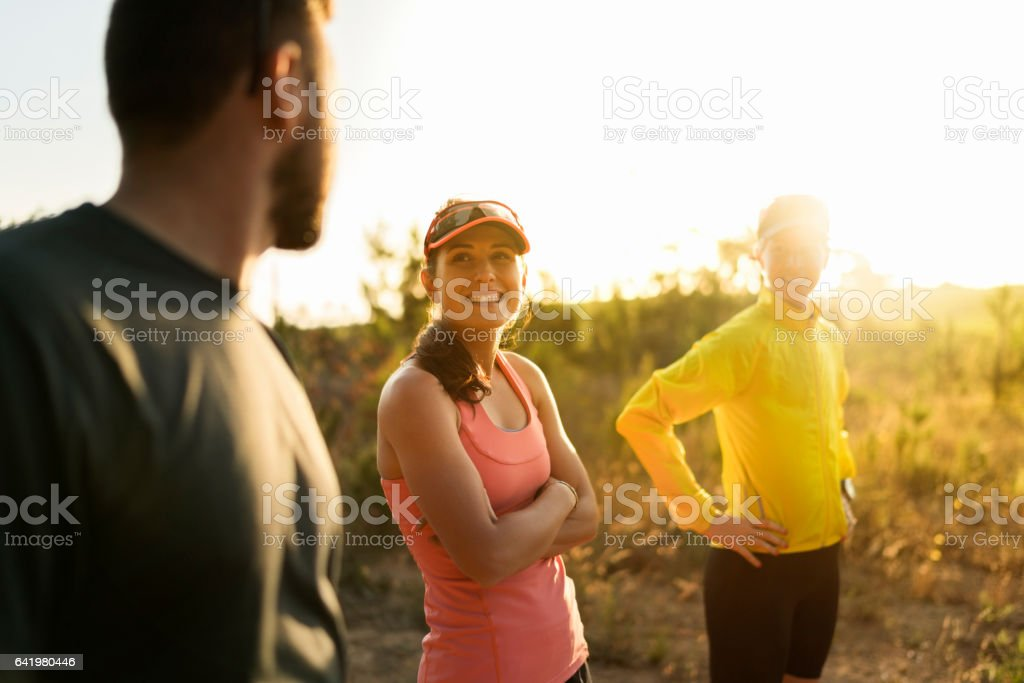 Smiling sporty woman looking at friend on field stock photo