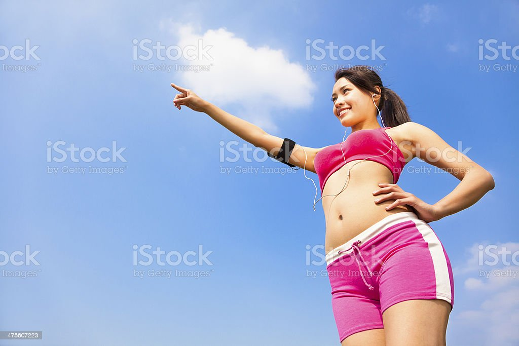 smiling sporty woman watching and pointing far away royalty-free stock photo