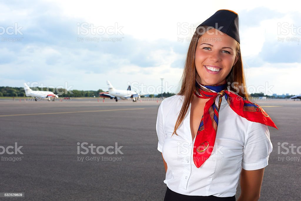 Smiling stewardess on the airfield stock photo