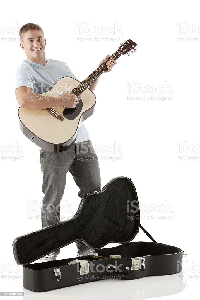 Smiling street musician playing a guitar royalty-free stock photo