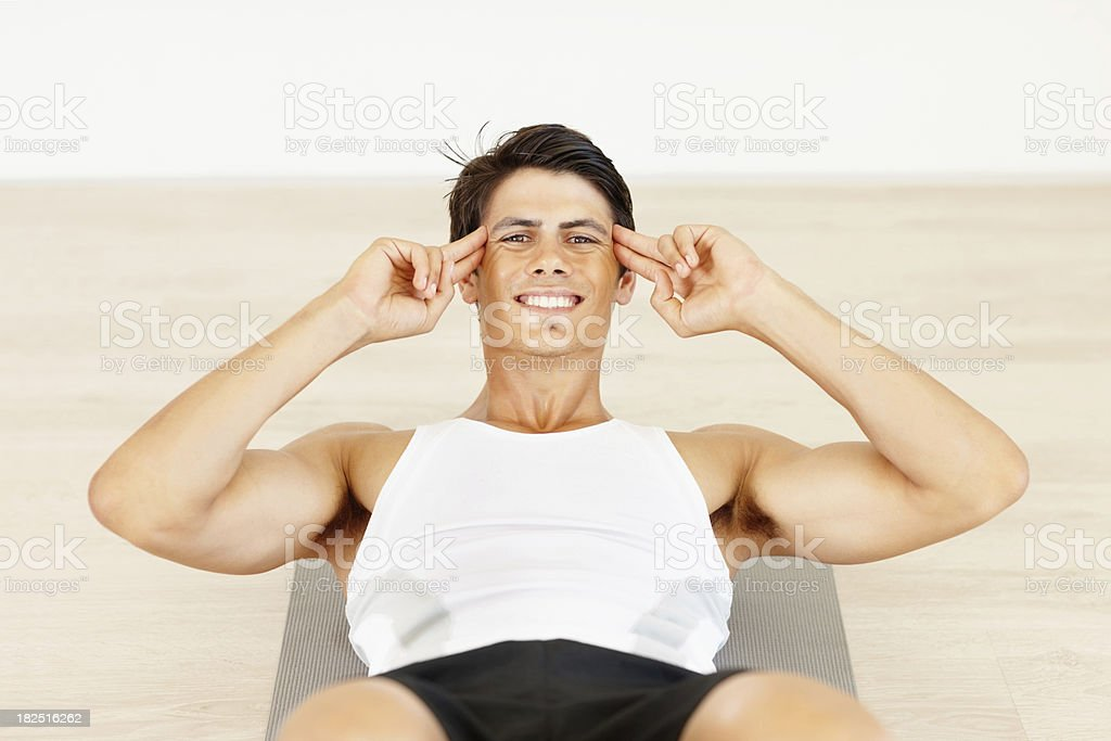 Smiling strong man working his abs at a gym royalty-free stock photo