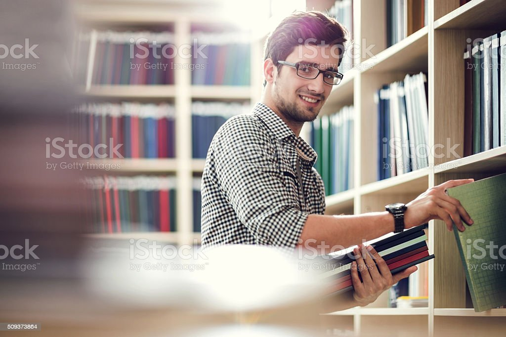 Smiling student choosing books in library and looking at camera. stock photo
