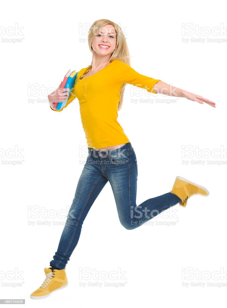 smiling student girl with books jumping stock photo