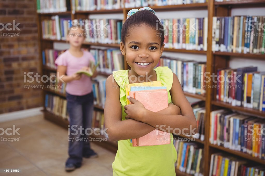 Smiling student holding a few books stock photo