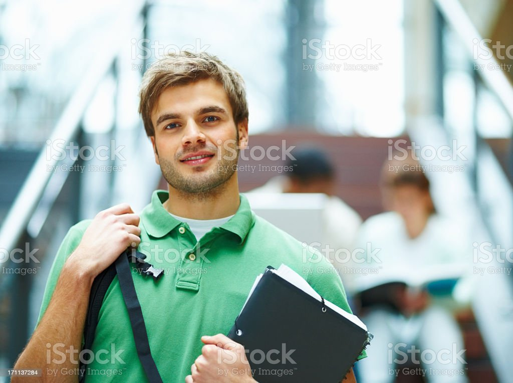 Smiling student holding books with students blurred behind stock photo