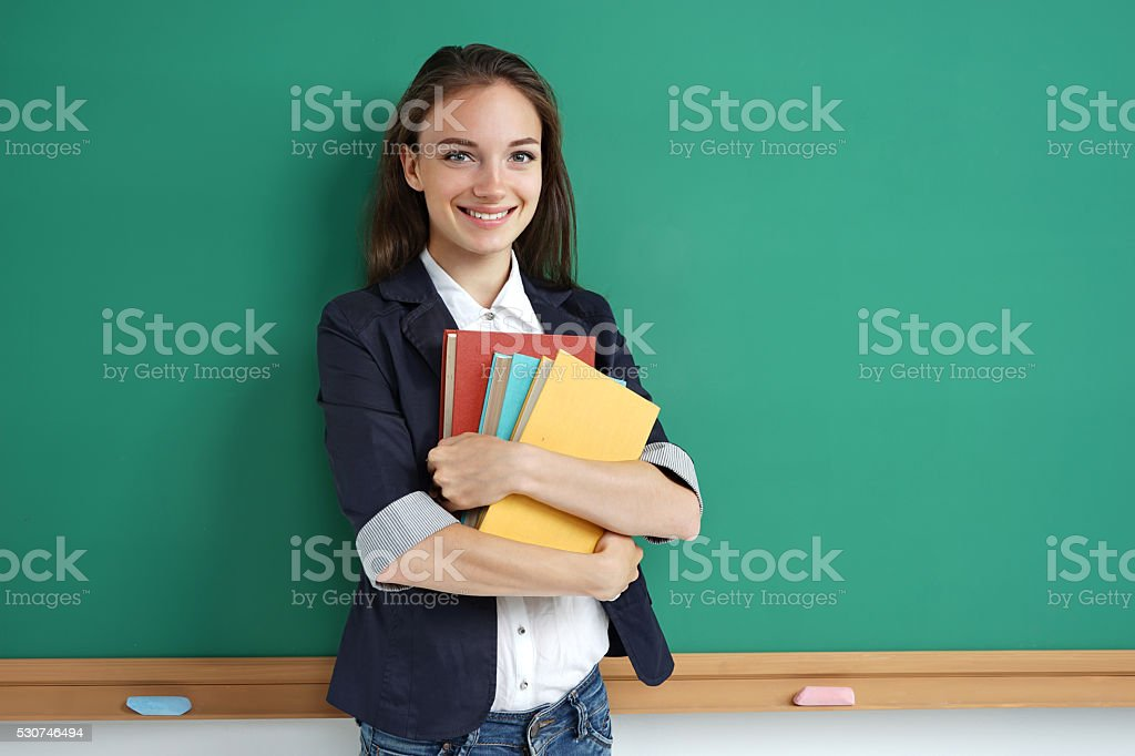 Smiling student hugging books. stock photo
