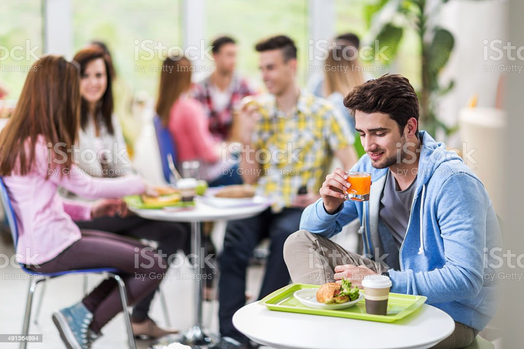 Smiling student on a lunch break drinking juice. stock photo