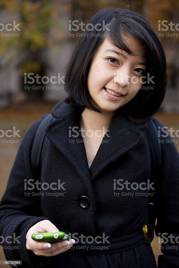 Smiling Student On Campus Holding Phone royalty-free stock photo