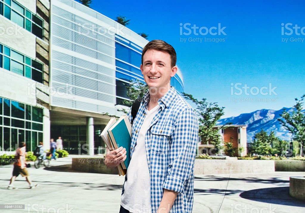 Smiling student outdoors and looking at camera stock photo