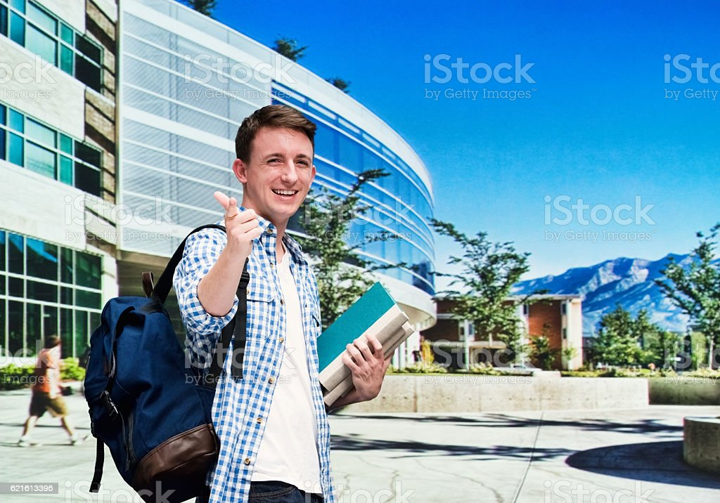 Smiling student pointing at camera stock photo