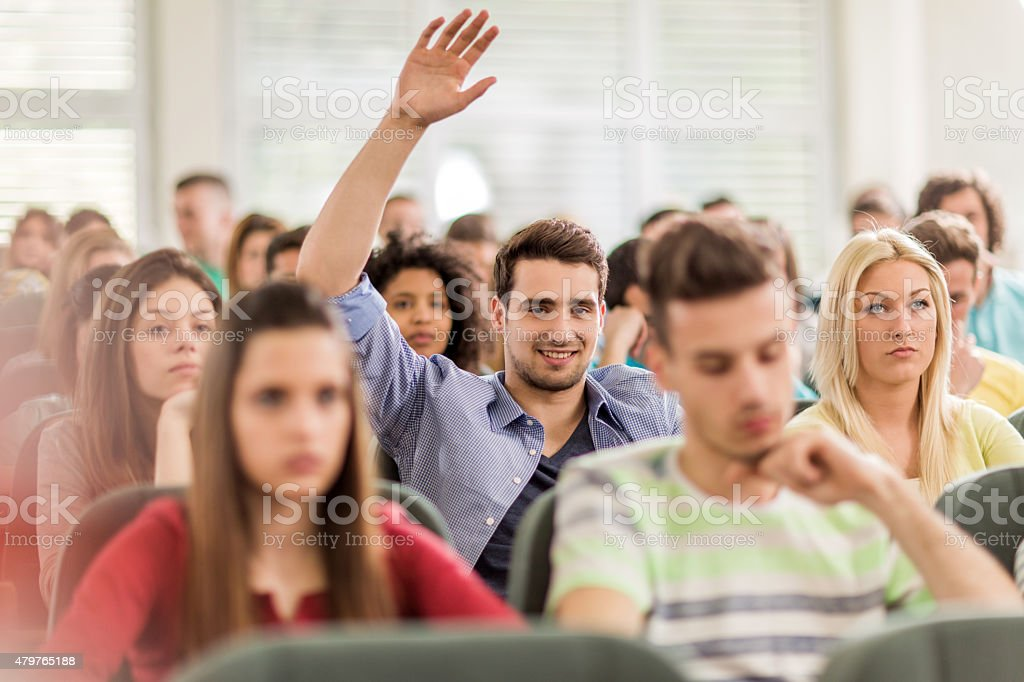 Smiling student raising hand to answer question at lecture hall. stock photo