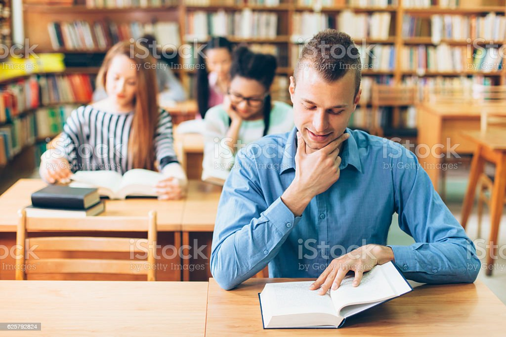 Smiling student reading a book at the library stock photo