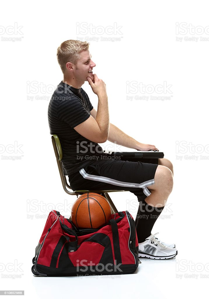 Smiling student sitting and looking away stock photo