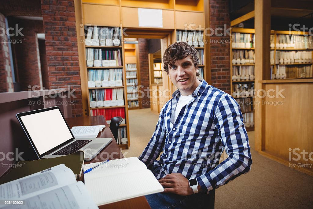 Smiling student sitting in library stock photo