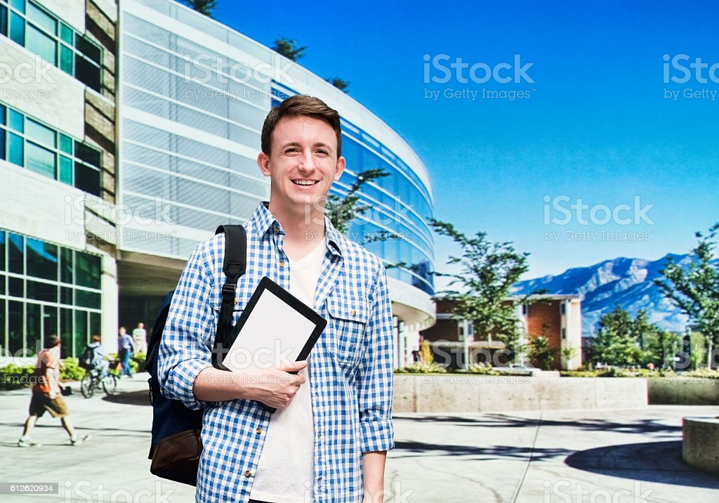 Smiling student standing at the campus stock photo