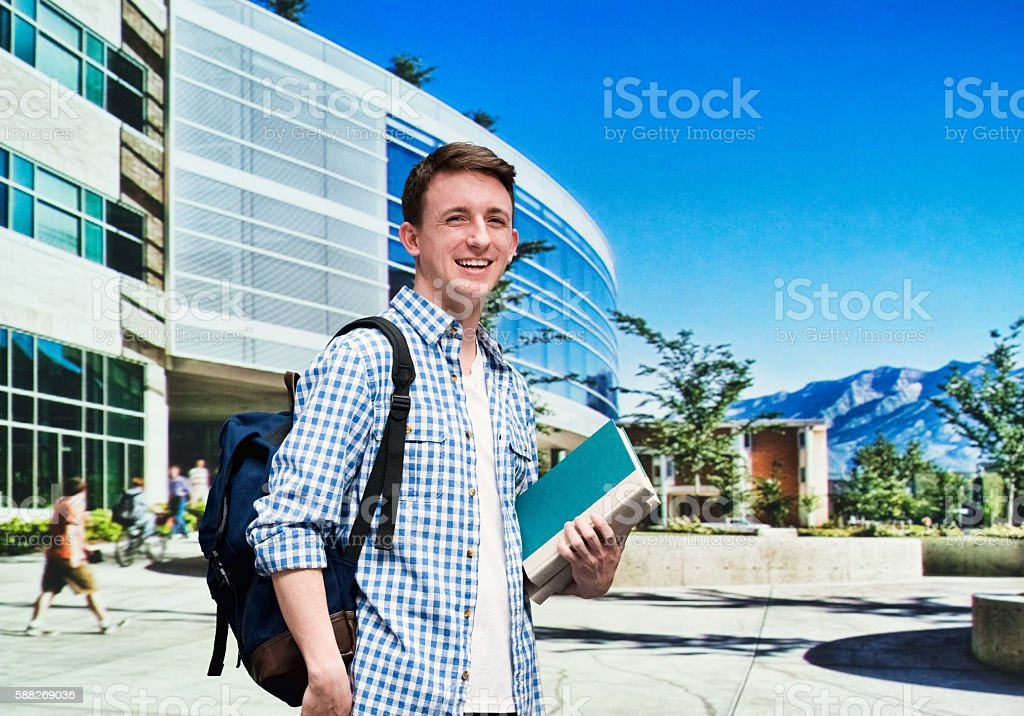Smiling student standing in campus stock photo