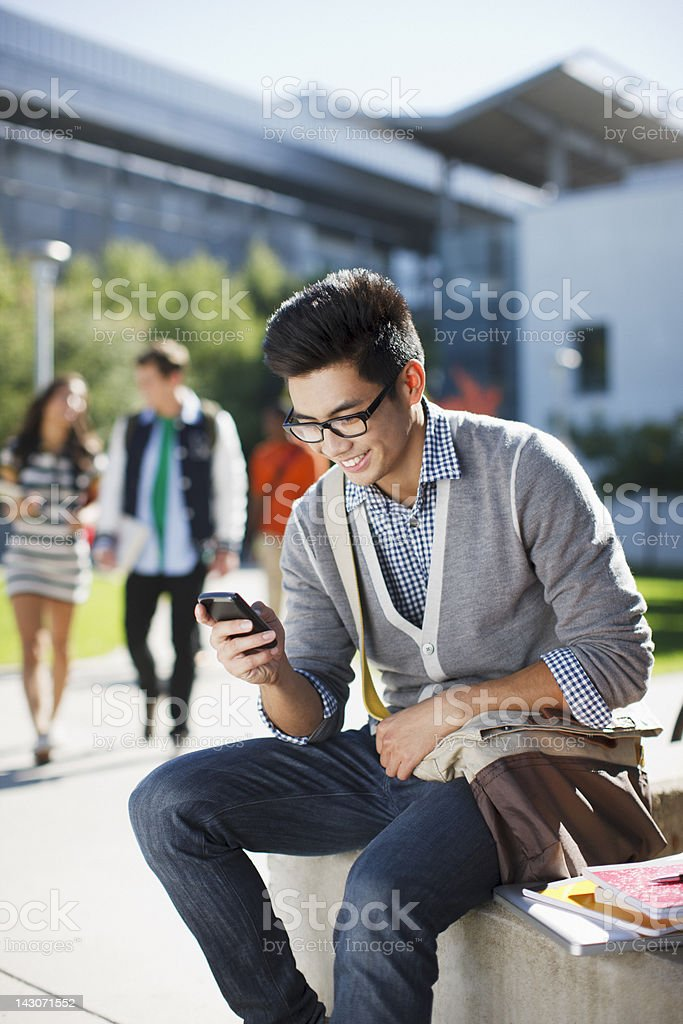 Smiling student using cell phone outdoors royalty-free stock photo