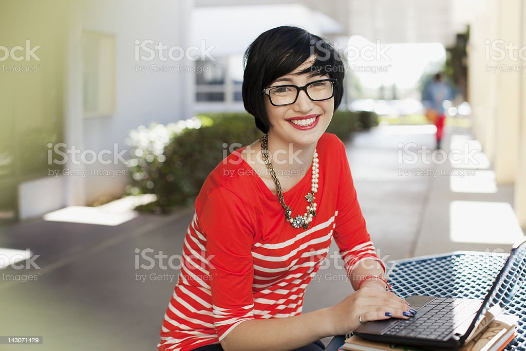 Smiling student using laptop outdoors royalty-free stock photo