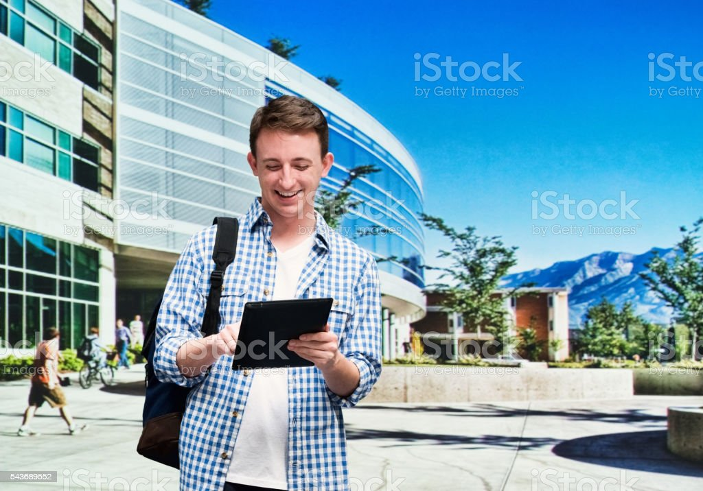 Smiling student using tablet in university campus stock photo