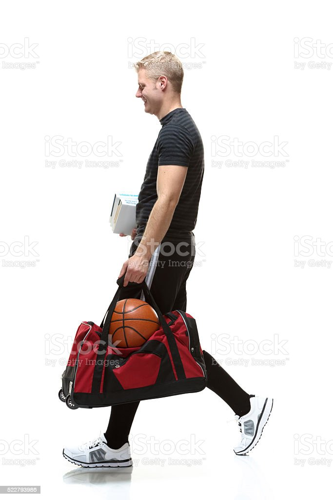 Smiling student walking with books and duffel bag stock photo