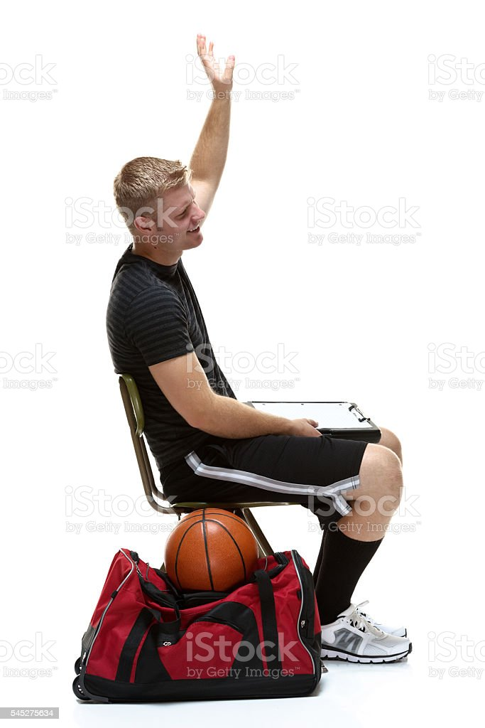Smiling student waving hand and sitting on chair stock photo