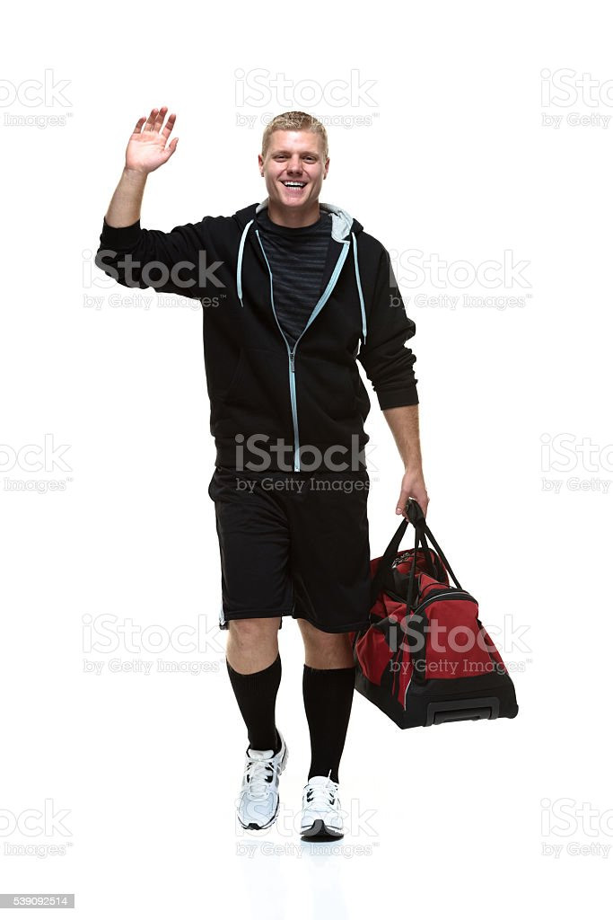 Smiling student waving hand and walking stock photo
