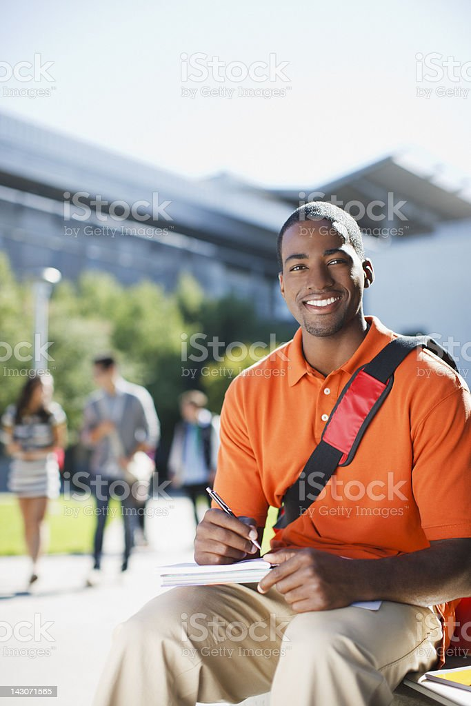 Smiling student writing outdoors royalty-free stock photo