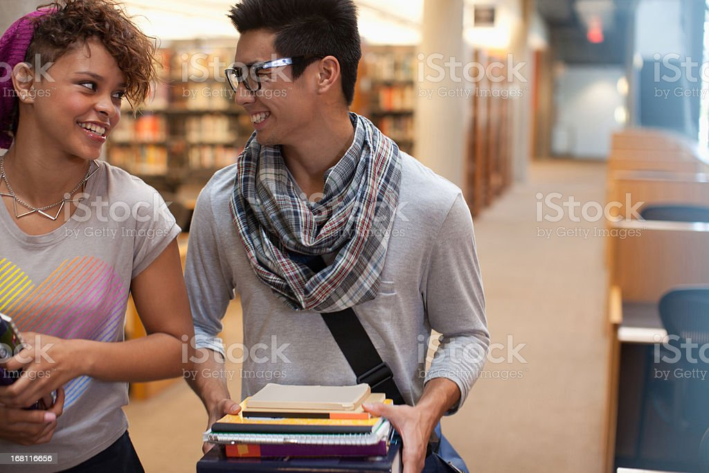 Smiling students talking in library royalty-free stock photo