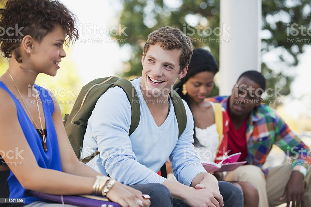 Smiling students talking outdoors royalty-free stock photo