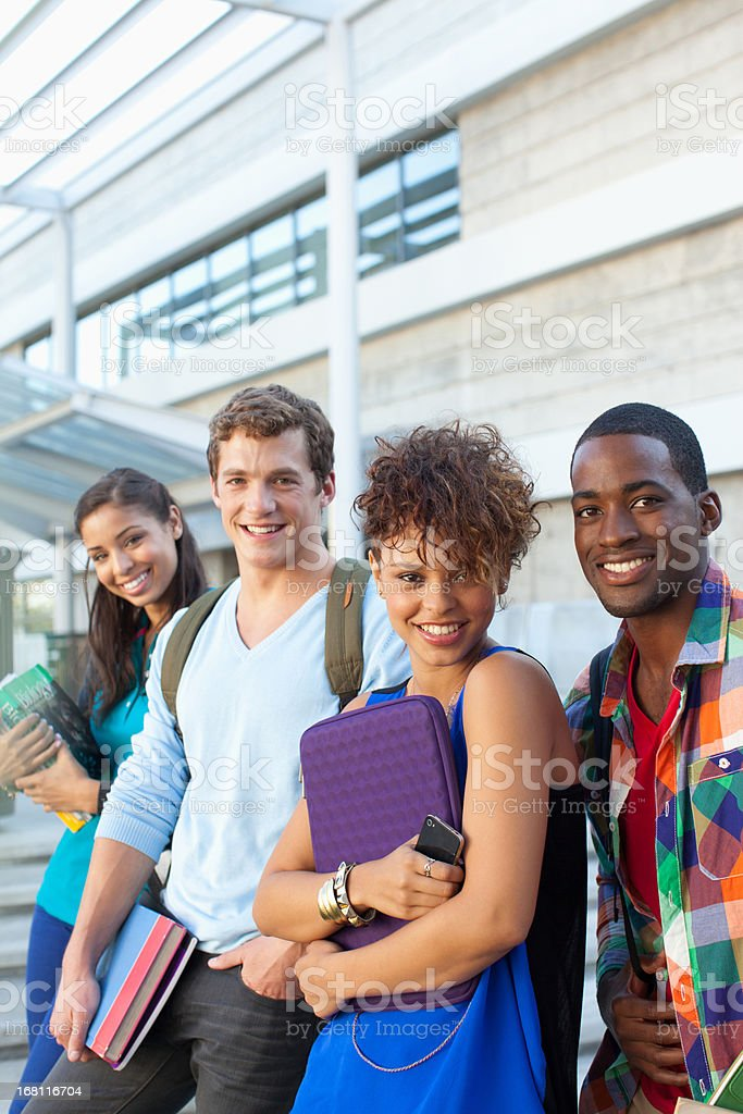 Smiling students talking outdoors stock photo