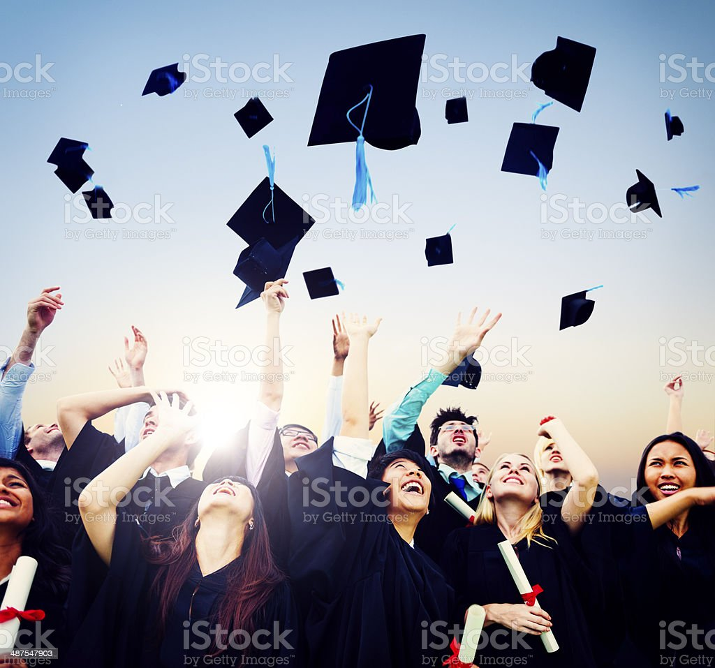 Smiling students throwing graduation caps in air stock photo