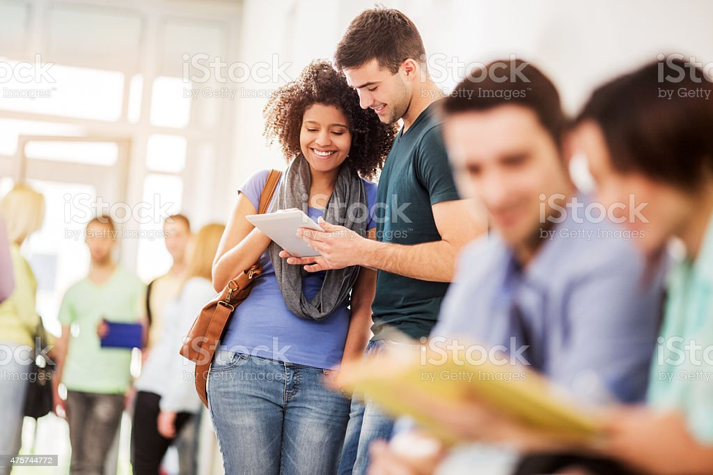 Smiling students using touchpad on a break. stock photo