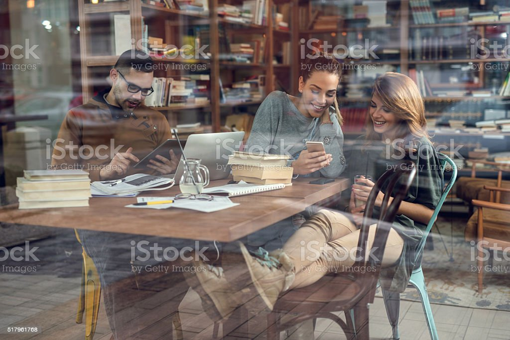 Smiling students using wireless technology in the library. stock photo